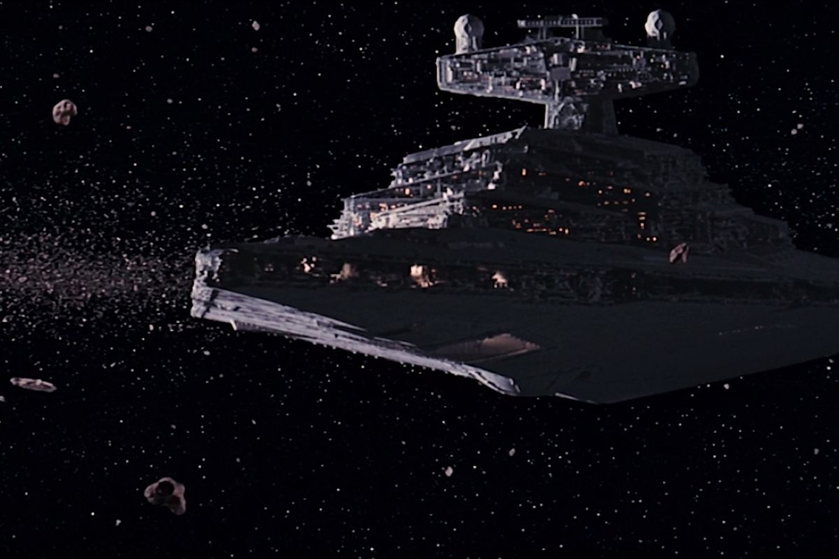 An Imperial Star Destroyer chases the Millennium Falcon in a still from The Empire Strikes Back