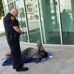 Salt Lake Police Officer Stone writes a homeless man a citation for trespassing in Salt Lake City on Thursday, Sept. 29, 2016. A joint operation by Salt Lake City and Salt Lake County in the downtown area is underway in an effort to immediately affect public health and safety there.