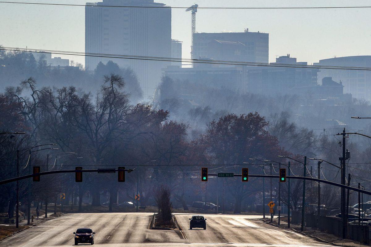 Hazy air pollution shrouds downtown Salt Lake City as cars move along Beck Street near 400 West on Monday, Dec. 7, 2020.