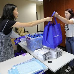 Hannah Segura, Mountain Heights Academy student services, hands a bag of supplies to 10th grader Lily Arnspiger during in-person orientation at Mountain Heights Academy, an online school based in West Jordan, on Tuesday, Aug. 24, 2021.