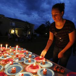 Shanell Johnson grabs a candle as friends gather during a candle light vigil in Logan Thursday, July 10, 2014. Ronald Lee Haskell, a recent Logan resident, has been charged with multiple counts of capital murder in a shooting in Texas. Haskell and his family lived in Logan for several years.