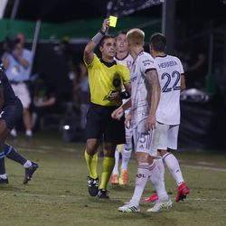 Referee Alex Cailowicz, center, issues a yellow card to Real Salt Lake defender Aaron Herrera (22) as defender Justen Glad (15) looks on during the first half of a soccer match against Minnesota United in Kissimmee, Fla., Friday, July 17, 2020.