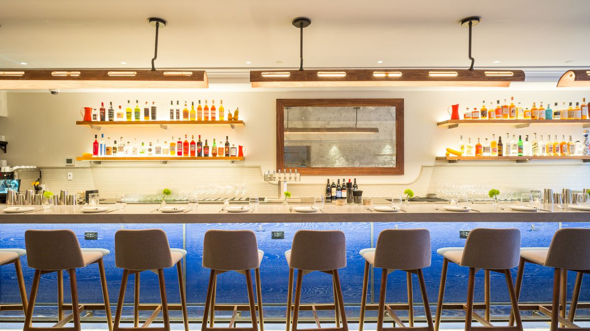 A backlit, blue toned bar with a line of empty chairs