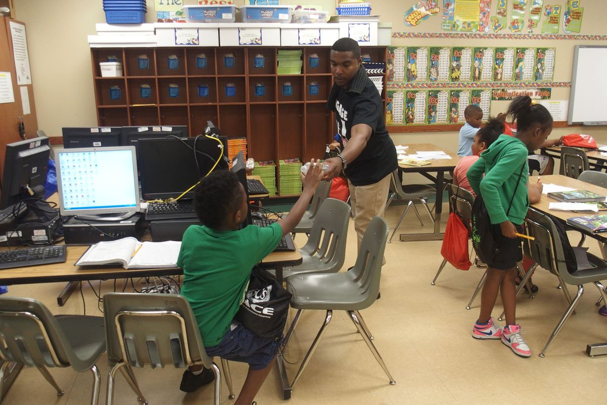 An engagement team member for Shelby County Schools hands out packets filled with reading books and district paraphernalia to children during a summer school program at Winridge Elementary School in Memphis.