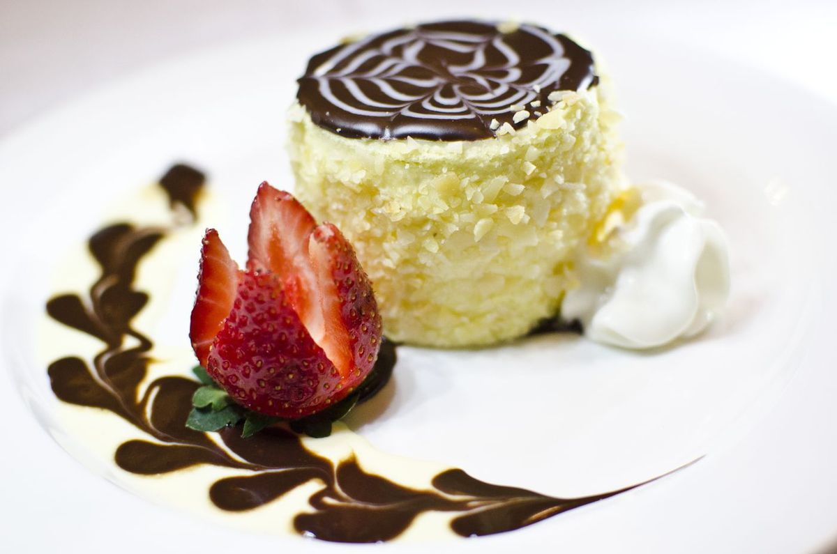 A mini round Boston cream pie, which is yellow cake with a milk chocolate and white chocolate glaze, sits on a white plate, garnished with a dollop of whipped cream, a strawberry, and chocolate sauce drizzled into a line of heart shapes