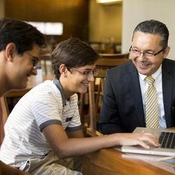 A senior missionary helps two young men research their family heritage on a computer.