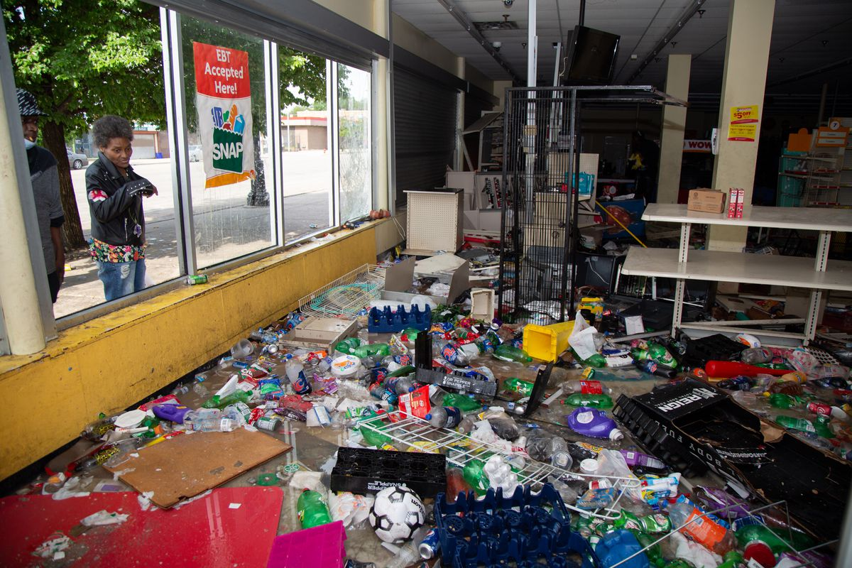 Passerbys peer through a destroyed window of a Family Dollar at 4247 W Madison St, in Chicago, Monday June 1, 2020.