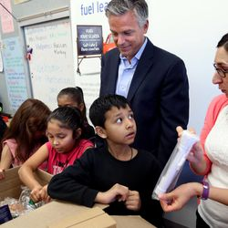 Former U.S. Ambassador to China, Utah Governor and current Chevron board of directors member Jon Huntsman Jr. helps students unwrap STEM-related teaching materials with teacher Melody Francis at Rose Park Elementary School in Salt Lake City on Wednesday, Sept. 3, 2014.