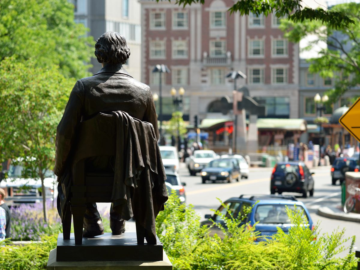 A statue of a man seated overlooking a busy square in a city.