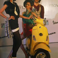 Models pose with a Vespa scooter during its launch in Mumbai, India, Thursday, April 26, 2012. The Italian company hopes to carve out a market for luxury scooters in one of the most cost-conscious markets in the world. The Vespa LX will cost around 66,661 rupees ($1,282) in India, a 40 percent premium to most scooters, but still the lowest sticker price in the world.