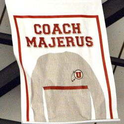 A banner replicating the late Coach Rick Majerus' trademark sweater is unfurled at the University of Utah's Huntsman Center in Salt Lake City on Saturday, Feb.2, 2013. Majerus, who passed away Dec. 1, coached the Utes from 1989-2004 — posting a 323-95 record and an appearance in the 1998 NCAA championship game.