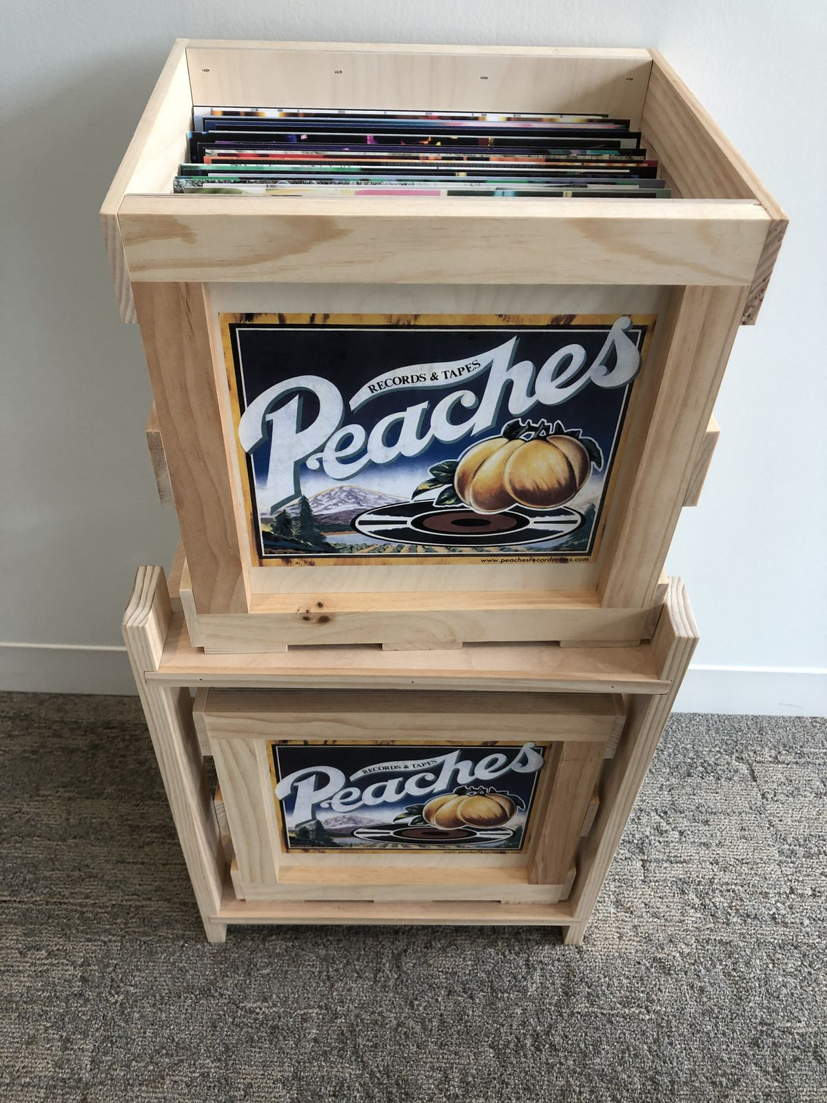 Two wooden crates with Peaches Records and Tapes labels containing vinyl records with white wall in background