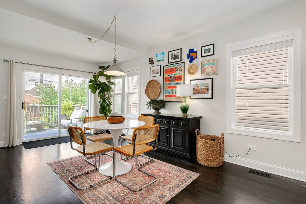 A gallery wall of colorful art and woven trays provides a focal point in the eat-in kitchen which shows the view to the backyard and a white circular table with four stylish metal and wicker chairs.