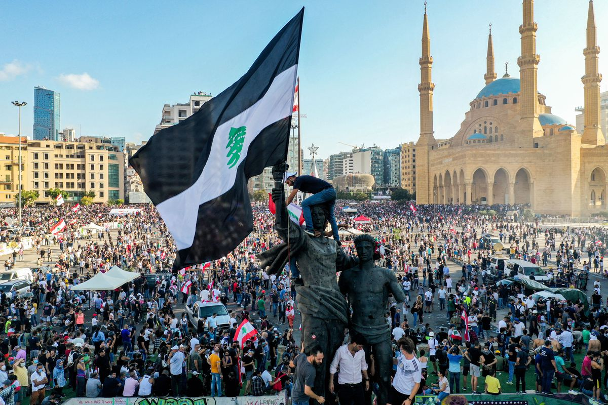 A protester climbs a statue of men with their arms raised up, planting a special Lebanese flag atop the monument. The flag normally has a red stripe on the top and bottom, and a white stripe with a green cedar tree in the middle. In this flag, the red stripes are replaced with black ones. Behind the monument is a mass of people, leading up to the blue dome of the Mohammad Al-Amin Mosque.
