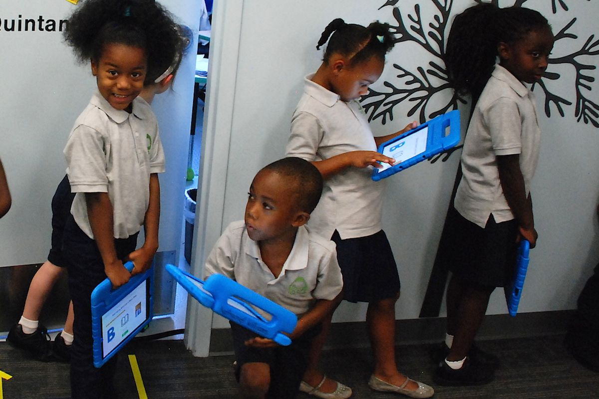 Roots Elementary students hold iPads as they stand in line to go into one of the school's mini-classrooms.