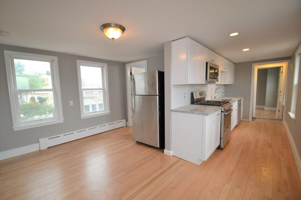 An open living room-kitchen area, with the fridge around the corner from the kitchen counter.