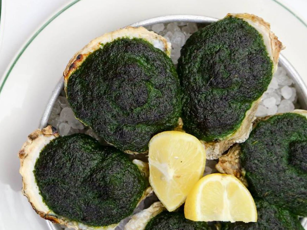 A dish of six oysters covered in a green baked sauce
