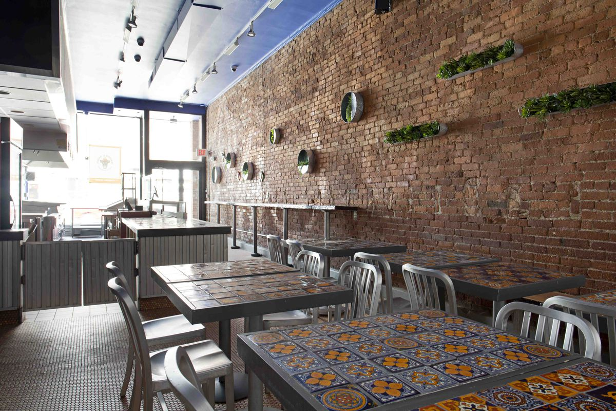 An interior photo of a small, counter-service Mexican restaurant, featuring a brick wall and tables decorated with colorful talavera tiles