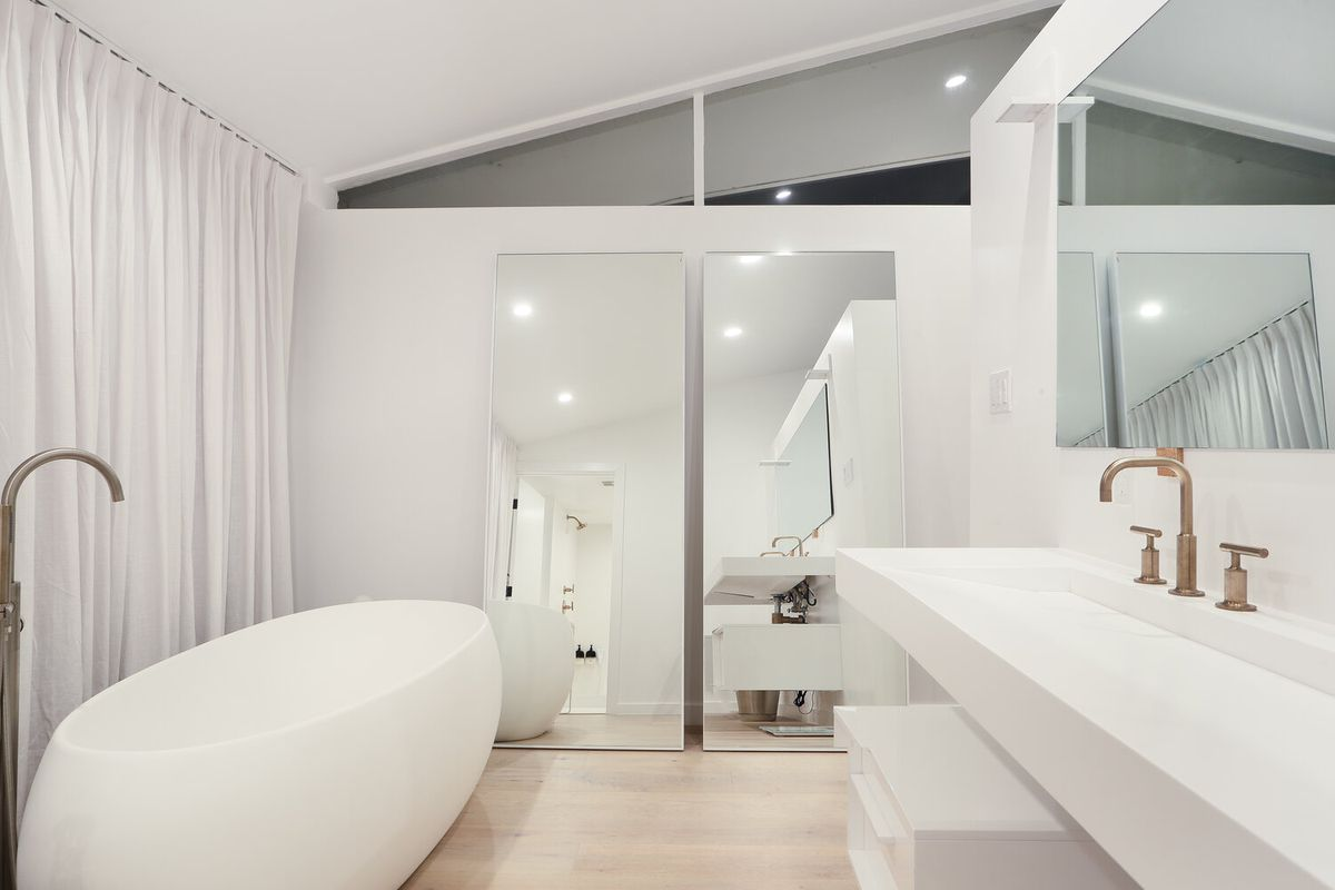 An egg-like soaking tub and a long, trough-like sink are the two stand-out features of the bathroom.