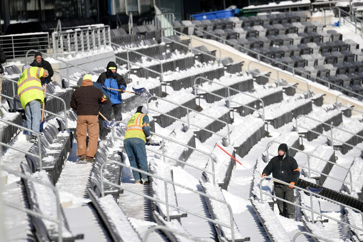 Workers clear snow from the MetLife Stadium stands on Wednesday