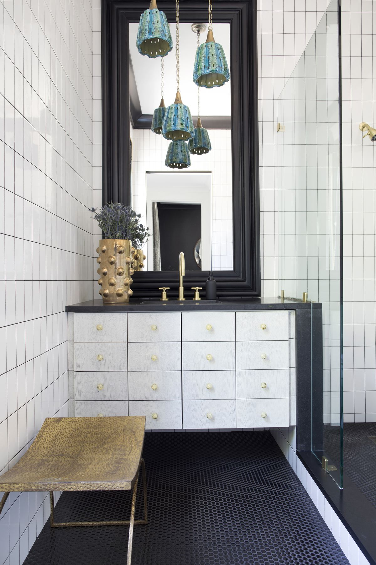 A white-and-black bathroom features a trio of turquoise pendants.