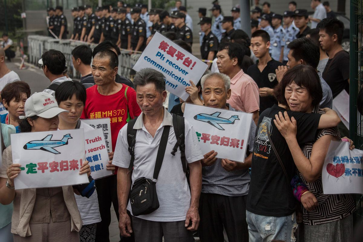 : Chinese relatives of passengers missing on Malaysian Airlines flight MH370 react outside the Malaysian Embassy during a protest by relatives on August 7, 2015, in Beijing, China.