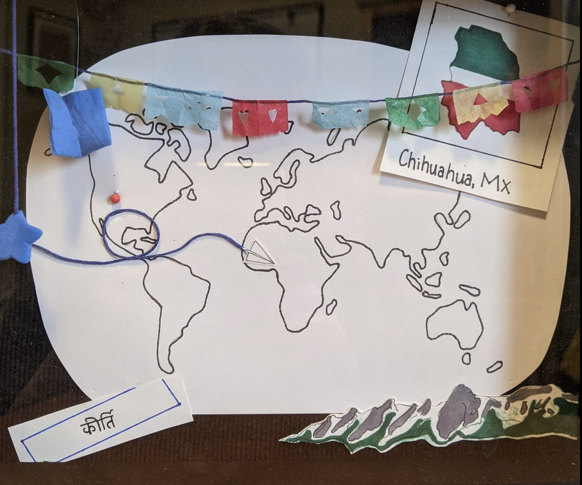 The inside of Isa Brady's shadow box including a world map she drew and papel picado draped over it.