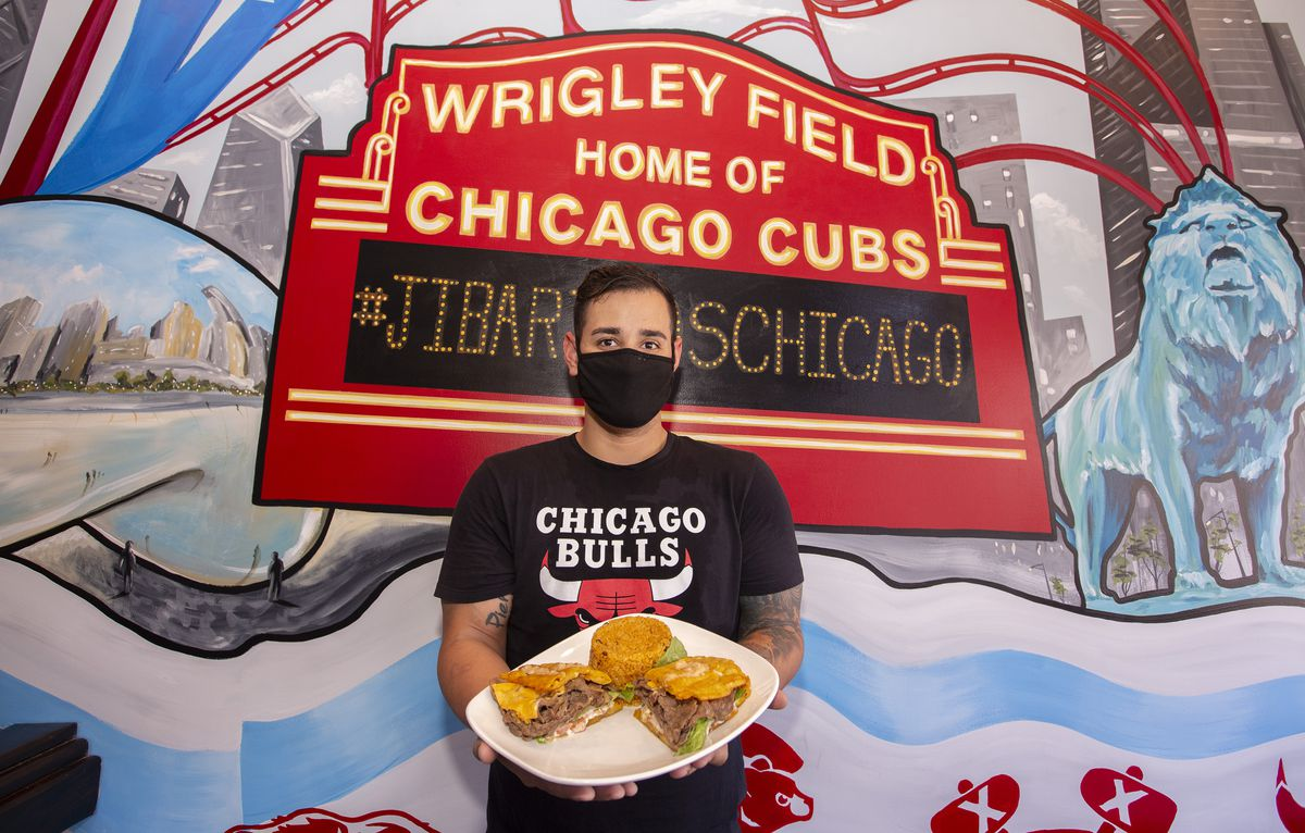 A man in a black mask and black Chicago Bulls t-shirt stands in front of a wall painted with a mural of the big red Wrigley Field sign holding a plate of jibaritos.