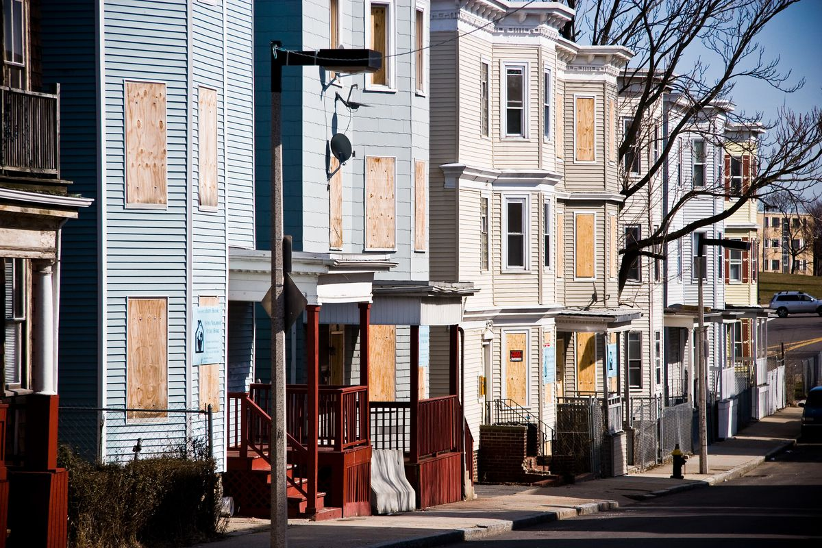A row of rowhouses with their windows boarded up.