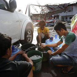 Men gather water in Tacloban, Friday, Nov. 22, 2013.