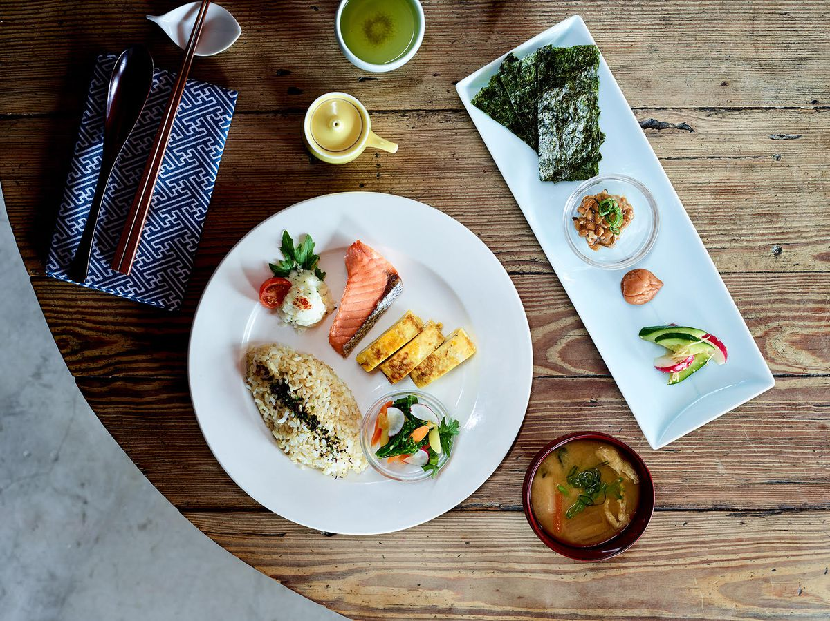A round plate with portions of rice, tamago, and cut vegetables next to a rectangular plate with seaweed, nuts, and sliced cucumber, and a cup of soup, plus soy sauce container with spout and a blue napkin with chopsticks, all on a wooden table