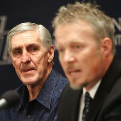 Utah Jazz coach Jerry Sloan listens to Greg Miller after announcing his resignation after being the head coach for the Jazz since 1988.