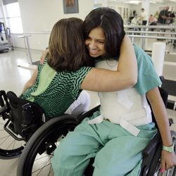 Tere Parra, right,  hugs Katie Terry-Corbridge after receiving her  donated titanium wheelchair  in Provo Wednesday, July 18, 2012. Parra was visiting from Mexico, fell from a tree and is now paralyzed.