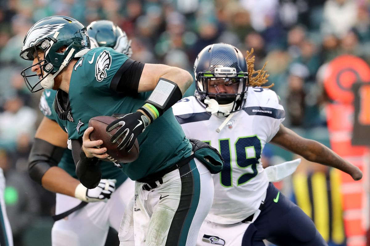 Carson Wentz of the Philadelphia Eagles scrambles as Shaquem Griffin of the Seattle Seahawks defends in the fourth quarter at Lincoln Financial Field on November 24, 2019 in Philadelphia, Pennsylvania.
