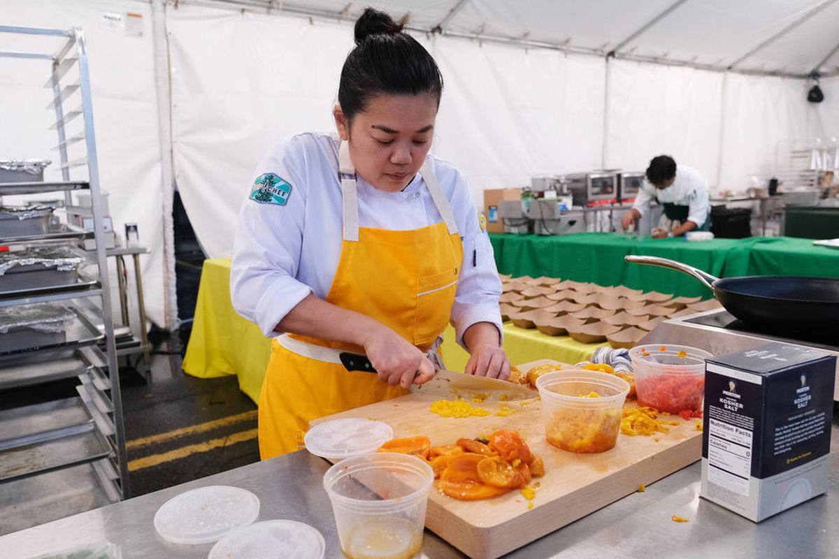 A woman with a white coat and yellow apron prepares a dish