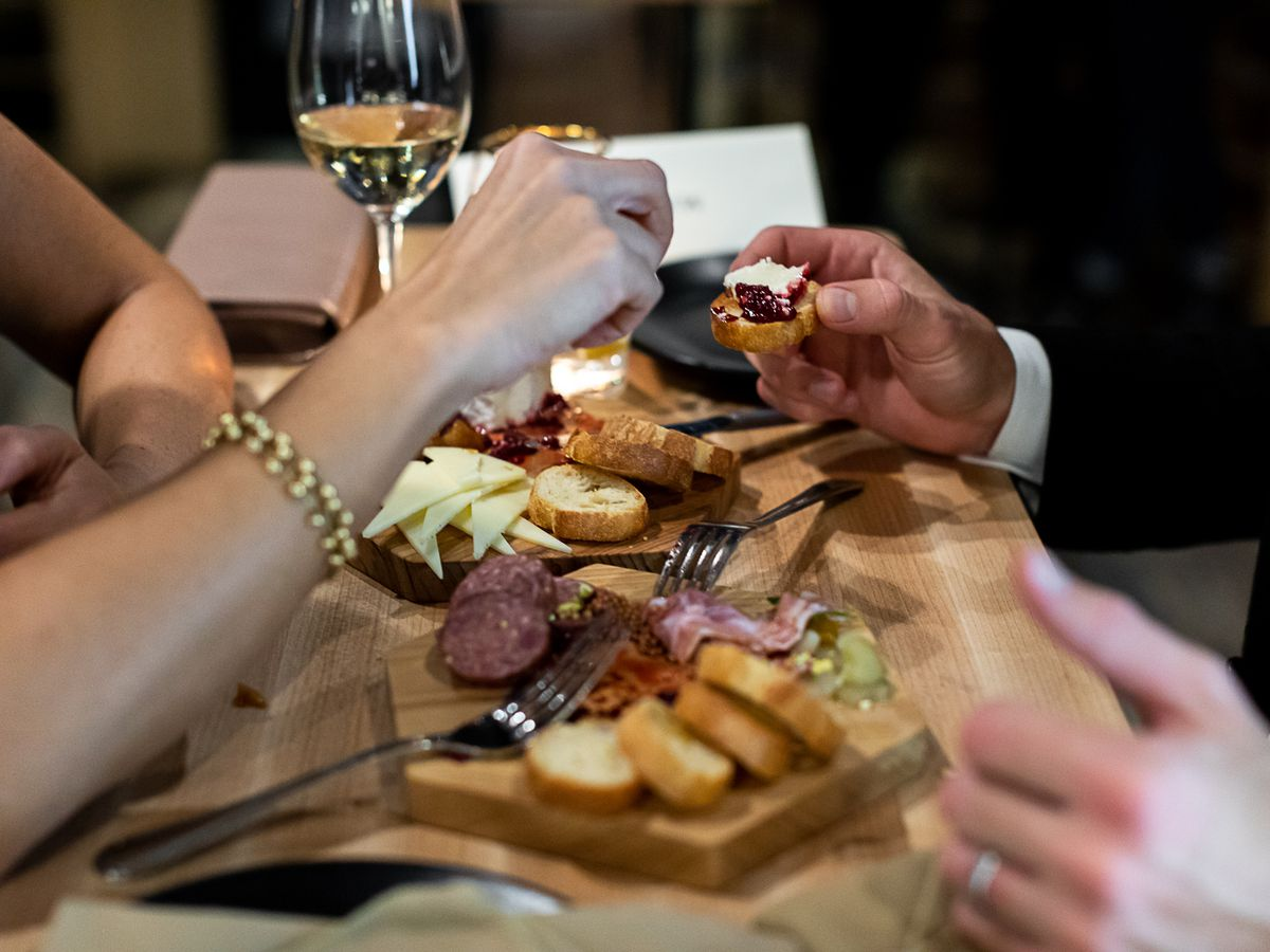 A couple eats charcuterie while sipping glasses of white wine.
