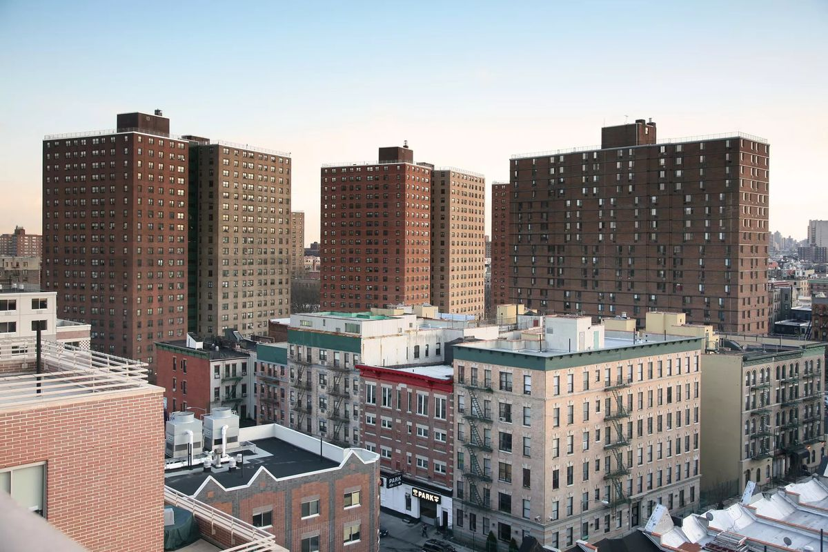 Three brown, high-rise public housing buildings loom over a handful of white low-rise apartment buildings in Manhattan.