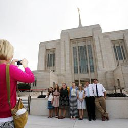 Allison Gonzales takes photos of some members of the Fisher and Turner families outside the Ogden Utah Temple in Ogden, Tuesday, July 29, 2014.