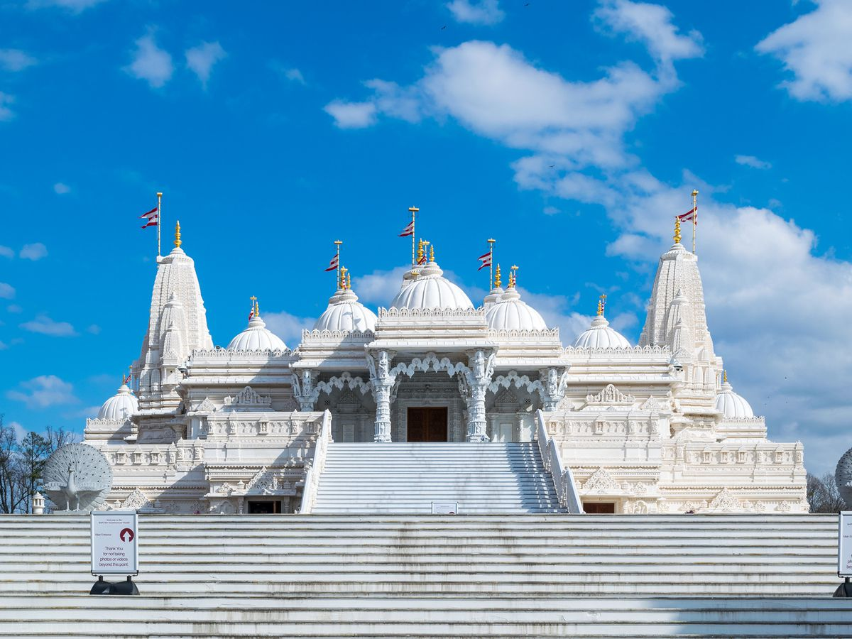 An extremely large Hindu temple made from white marble with flags on its peaks