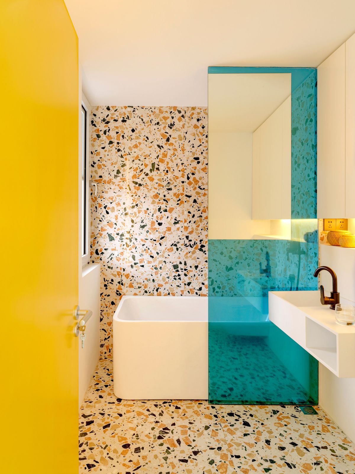 Bathroom with terrazzo floors and walls, yellow door, and blue glass.