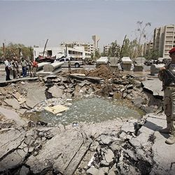 An Iraqi soldier stands guard at a bomb site in front of the Iraqi Foreign Ministry in Baghdad, Iraq Saturday.  Iraqi Foreign Minister Hoshyar Zebari said Saturday that those who carried out bombings that targeted government buildings in the Iraqi capital received help to pull off the attacks, possibly from Iraqi security forces.