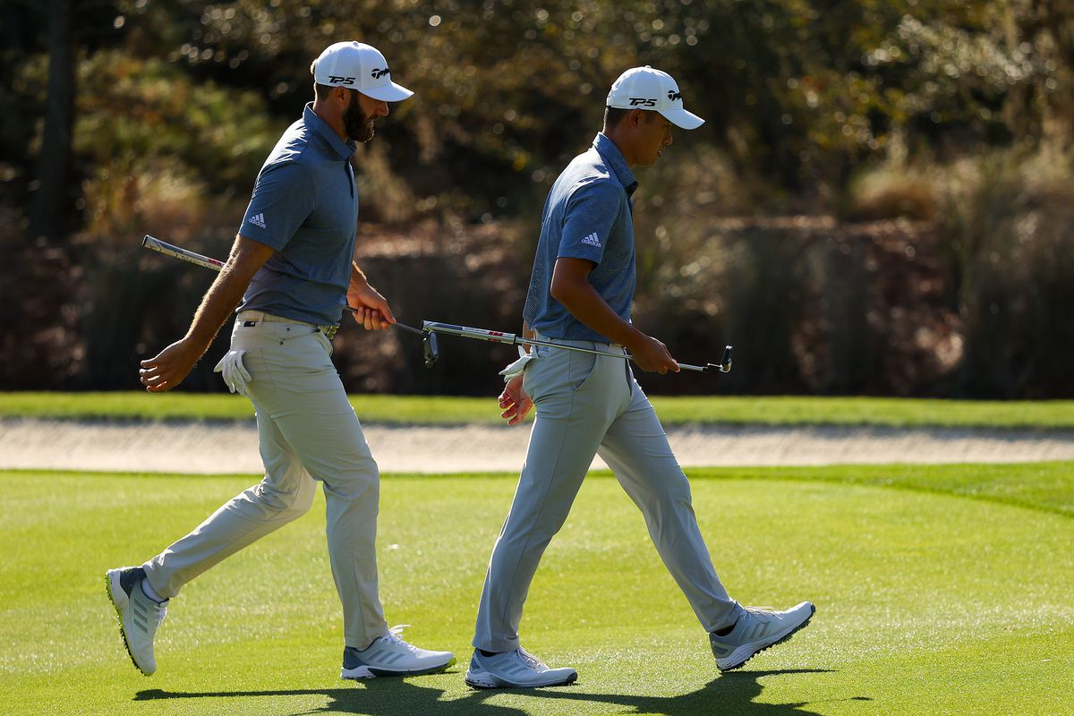 Dustin Johnson of the United States and Collin Morikawa of the United States walk on the 14th hole during the second round of THE PLAYERS Championship on THE PLAYERS Stadium Course at TPC Sawgrass on March 12, 2021 in Ponte Vedra Beach, Florida.