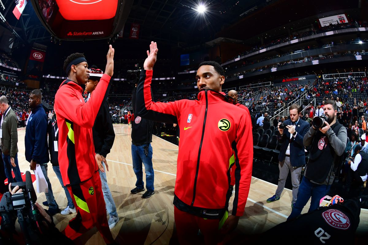 De'Andre Hunter and John Collins of the Atlanta Hawks hi-five prior to a game against the Philadelphia 76ers on January 30, 2020 at State Farm Arena in Atlanta, Georgia.