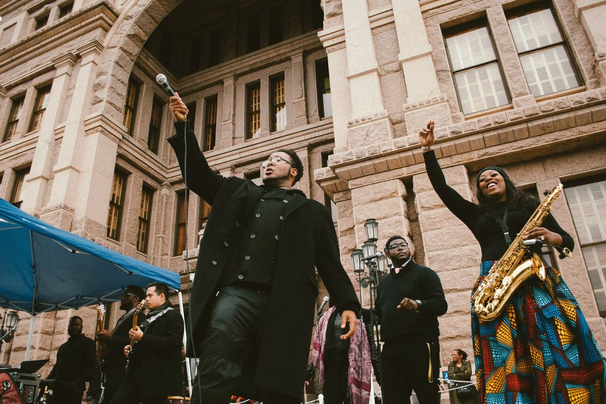 Musicians holding hands, microphone in air in front of state Capitol