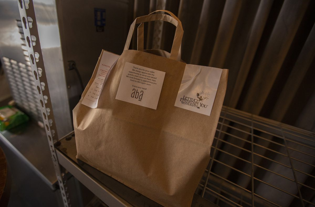 A brown paper bag full of food from Aba