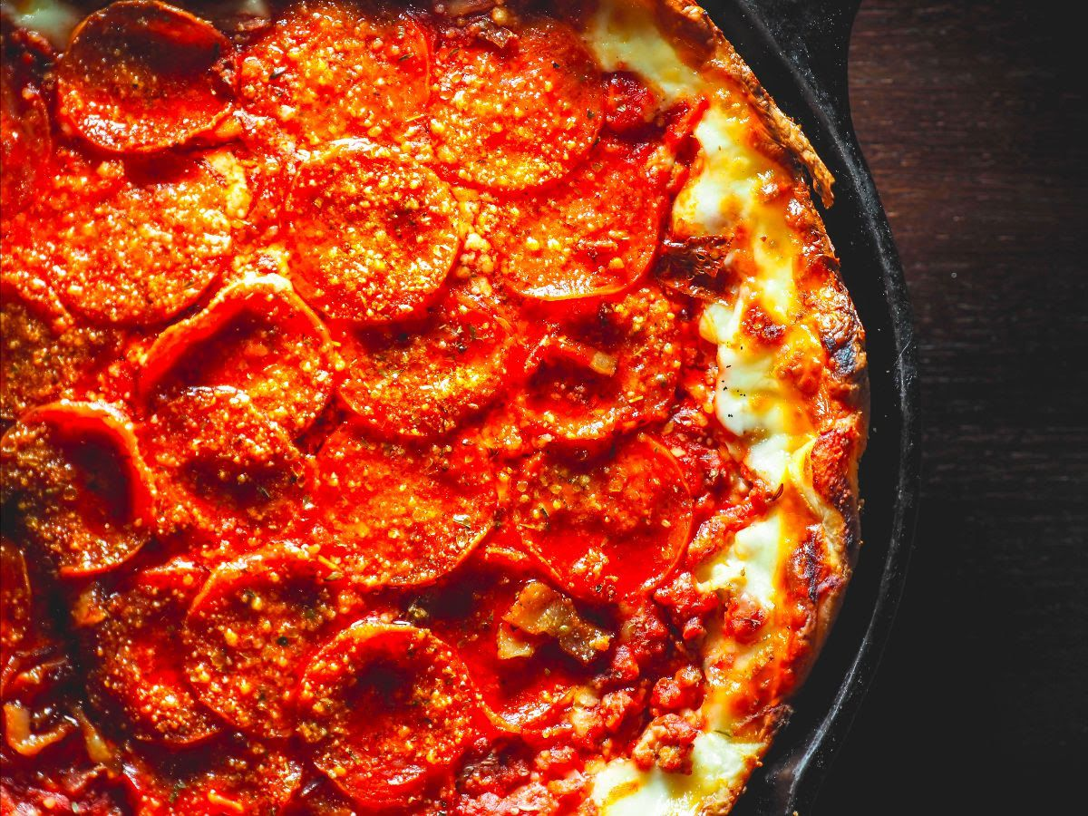 A deep dish pizza piled with pepperoni
