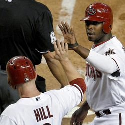 Arizona Diamondbacks' Justin Upton, right, and Aaron Hill high-five after scoring against the Philadelphia Phillies on a double by Cody Ransom during the second inning of a baseball game Monday, April 23, 2012, in Phoenix.