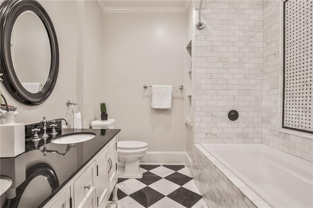 A white bathroom with checkerboard floors.