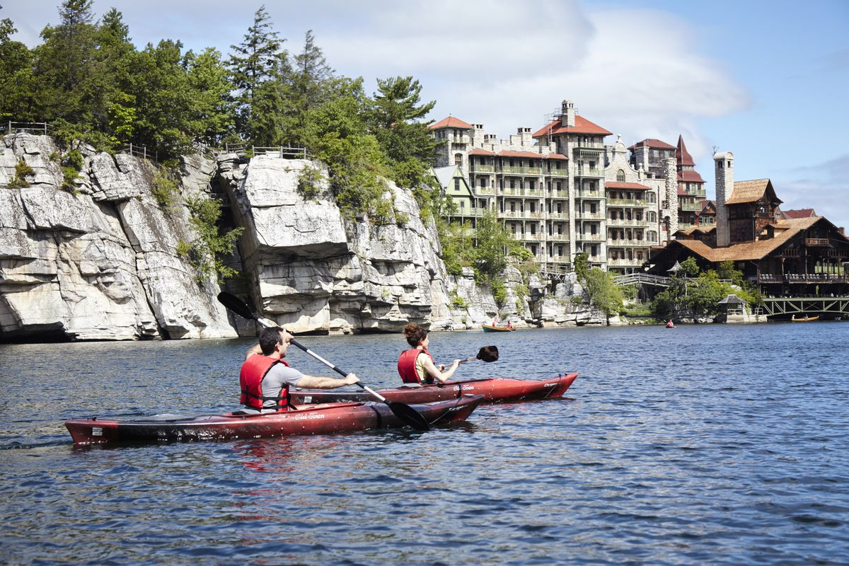 In the foreground two people are in kayaks on a body of water. In the distance is a large house with a rock cliff to the side of it.