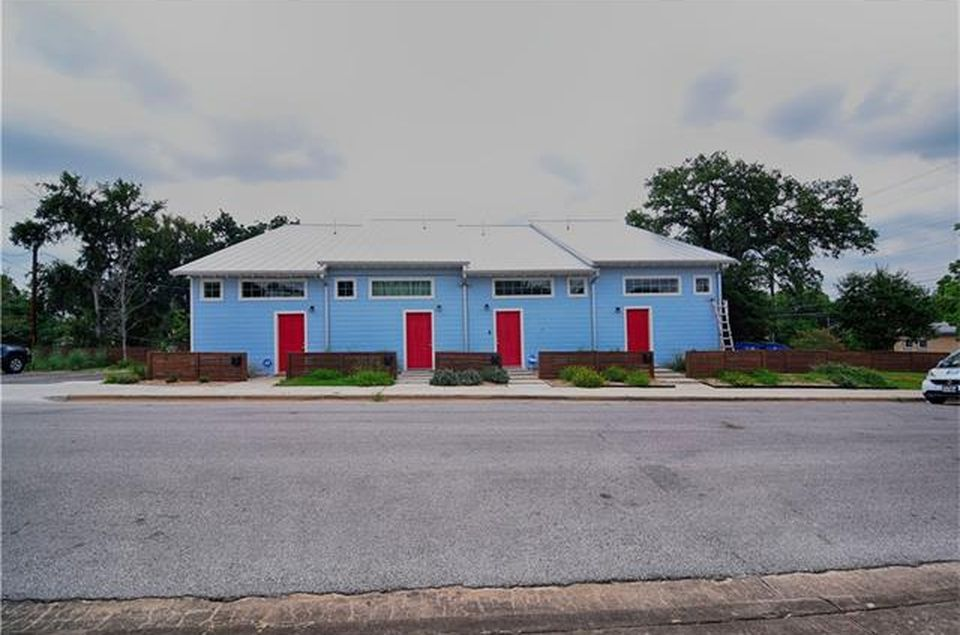 Long, low building painted bright blue with four red doors